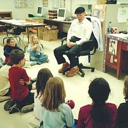 Aurélien Dupuis en salle de classe, des enfants par terre en demi-cercle devant lui.