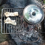Two fillets next to a small backpacking pot, cooking on a campfire grill.