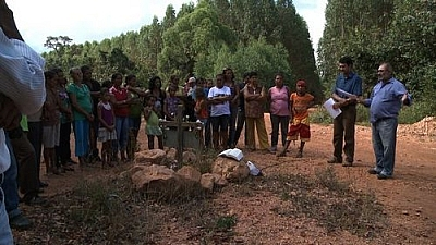 "Image from the film ""The Carbon Rush"": A group gathers around the grave of a murdered activist."