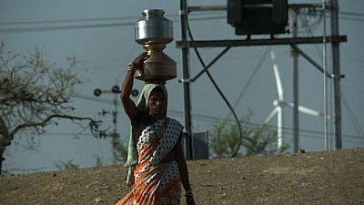 "Image from the film ""The Carbon Rush"": Woman carrying a large urn of water on her head."