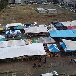 Top view of market stalls set up beneath colourful tarps.