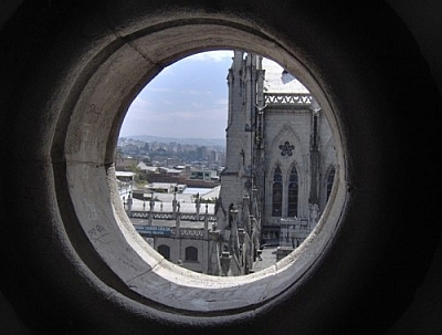 View of Quito through a round window of the Basilica del Voto Nacional.