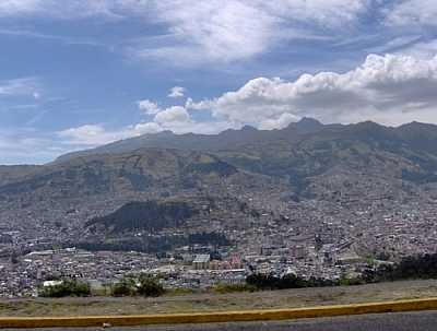 View of a city nestled in a valley, mountains in the backdrop and the shoulder of the highway visible in the foreground, depicting that the road is high up on a mountain above the city.