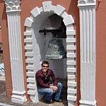 A short-haired young woman with no hair cares smiles proudly in the bell tower of the Monestario de Santa Catalina in Quito, Ecuador.