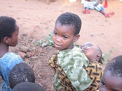 We know it's about all people when we see, as here, young children affected by AIDS gathered, one boy in the centre carrying an ill child on his back.