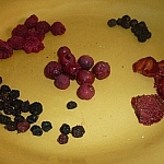 A variety of dehydrated berries in piles on a yellow plate