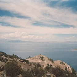 Gorgeous scenery of the vast Lake Titicaca beneath a wide open sky streaked with wispy clouds.