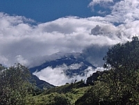 A cloud envelops a mountaintop in the sky (seen while travelling in South America).