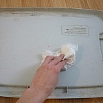 Wiping condensation from the lid of the vermicomposting bin with a paper towel.