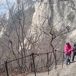 Korean hikers hanging on to a railing for dear life as they climb the steep side of Bukhan Mountain, which has many trails easily seen from Seoul.