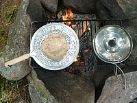 Cooking our trail flatbread on our hand toaster, which we simply place on a grill instead of holding.
