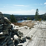 View of a white granite ridgetop, a rock cairn in the foreground, the cracks on the rock seeming to indicate the way along Killarney's La Cloche Silhouette Trail.