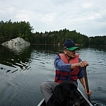 Marc paddling the canoe, Fetcher sitting in front of him.