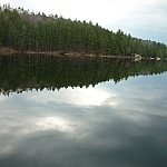 Trees lining the shoreline mirrored in Boundary Lake.