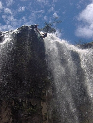 Climbing down the ledge of the last set of falls while repelling in Baños.