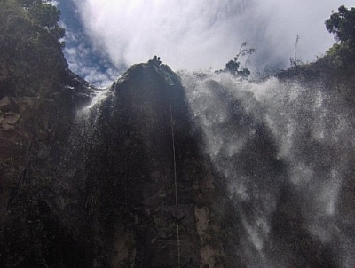 View from the bottom looking up at the last set of falls while repelling in Baños.
