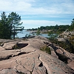 Dark cracks in the pink granite seem to move forward towards the pine-tree-lined shore of Georgian Bay.