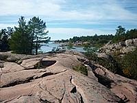 Dark cracks in the pink granite seem to move forward towards the pine-tree-lined shore of Georgian Bay.