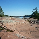 Smooth pink granite undulates towards Georgian Bay, barely visible beneath a bright blue sky.