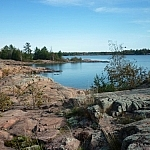 View of a pink granite shoreline hugging a small bay around to a point.