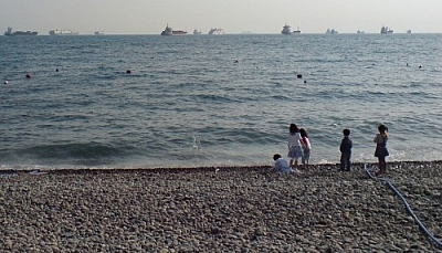 Children playing on a rocky beach with ships on the horizon, a water hose leading to the ocean from an unseen beach restaurant where ethical eating and vegetarian living in Korea is made that much easier.