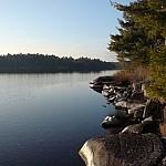 Wet rocks jut out into calm Lake Nipissing along the Coastal Trail.