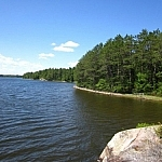 Wind ripples Lake Nipissing's dark blue waters beneath a bright blue sky along Coastal Trail.