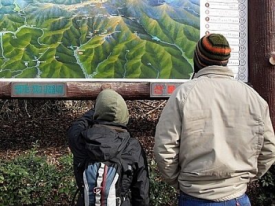 Consulting a large Korean park billboard map.