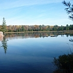 Panoramic view of the Cranberry Bog, which actually looks like a small lake, with deep blue water reflecting the colourful autumn trees near the shoreline.