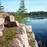 A large pink granite rock outcrop diagonally blocks Cranberry Bog from view, from top-left to bottom-right.