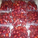 Nine plastic baggies full of strawberries.