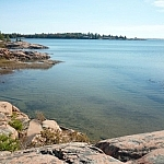 A pink granite shoreline hugs the clear shallow waters of Georgian Bay