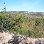 An autumn-coloured forest stands between Granite Ridge and a large white quartzite hill.