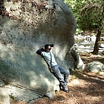 Leaning on a huge boulder at Grundy Lake Park while hiking in Ontario