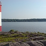 A red-and-white striped light beacon stands on on a rock outcrop protruding into Georgian Bay at Killbear Provincial Park near Parry Sound.