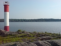 A red-and-white striped light beacon stands on on a rock outcrop protruding into Georgian Bay at Killbear Provincial Park near Parry Sound, Ontario.