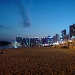 Haeundae Beach in the evening, lights from skyscrapers twinkling.