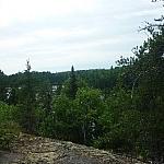 A lake just hidden by trees seen while day hiking Hawk Ridge Trail near Sudbury.