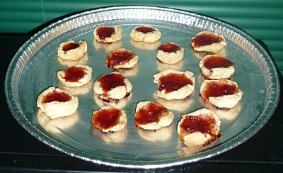 Jam cookies, a few of them with some bright red filling oozing out onto the baking sheet.