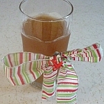 Glass of kombucha tea wrapped in a red, white, and green striped holiday bow.