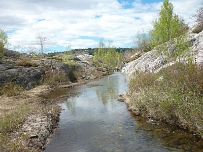 Beautiful scenery of a stream dumping seemingly into the sky while trekking Killarney's La Cloche Silhouette loop trail.
