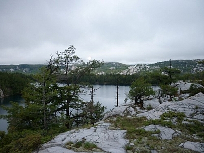 Sun and clouds over a lake and mountains while trekking Killarney's La Cloche Silhouette loop trail.