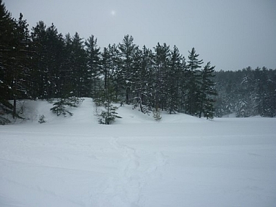 Sun shining hazily behind clouds while snowshoe hiking to The Lake Above in French River.