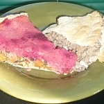 A slice of mixed veggie pie with mashed potato and red beet top crust, and a slice of meat pie, both siting on a small side plate.