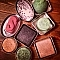 A variety of colourful Lush soaps displayed attractively in reusable tins.