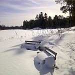 Snow-covered rest benches along the Loudon Peatland Trail.