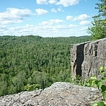 A vast forested expanse stretches beyond the edge of a rocky cliff.