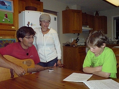 Sitting around the kitchen table with lyric sheets and a guitar.