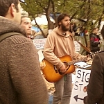 Crowd watching a musician playing guitar at Occupy Toronto.