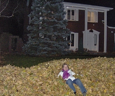 Jumping in piles of fallen leaves in a residential neighbourhood.